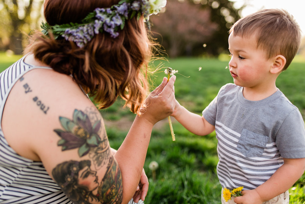 Mother blows dandelion with son at Loose Park, Kansas City lifestyle photographer, candid family photos, golden hour session, Rebecca Clair Photography