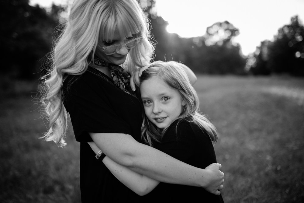 Mother and daughter embrace in the evening light, black and white portrait of mother and daughter, emotive family photos, Lee's Summit family photographer, golden hour session at Lake Jacomo, Rebecca Clair Photography