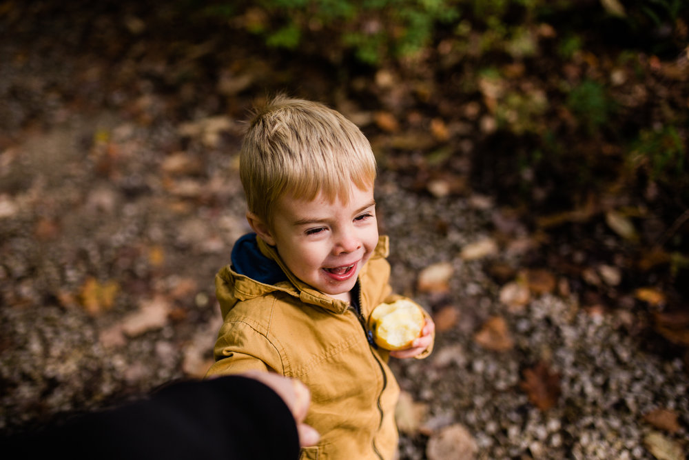 Boy walking holding mom's hand, autum walk in the woods, Kansas City family photographer, Lakeside Nature Center, Kansas City fall mini sessions