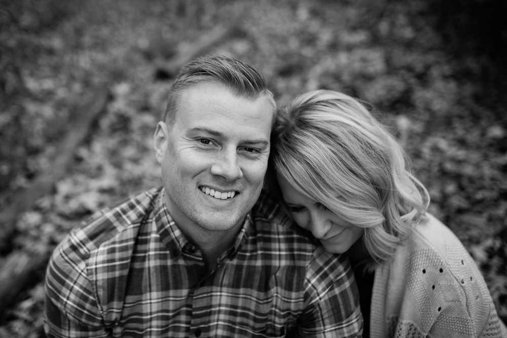 Black and white photo of a woman cuddling on her husband's shoulder, Kansas City candid portrait photographer, Rebecca Clair Photography