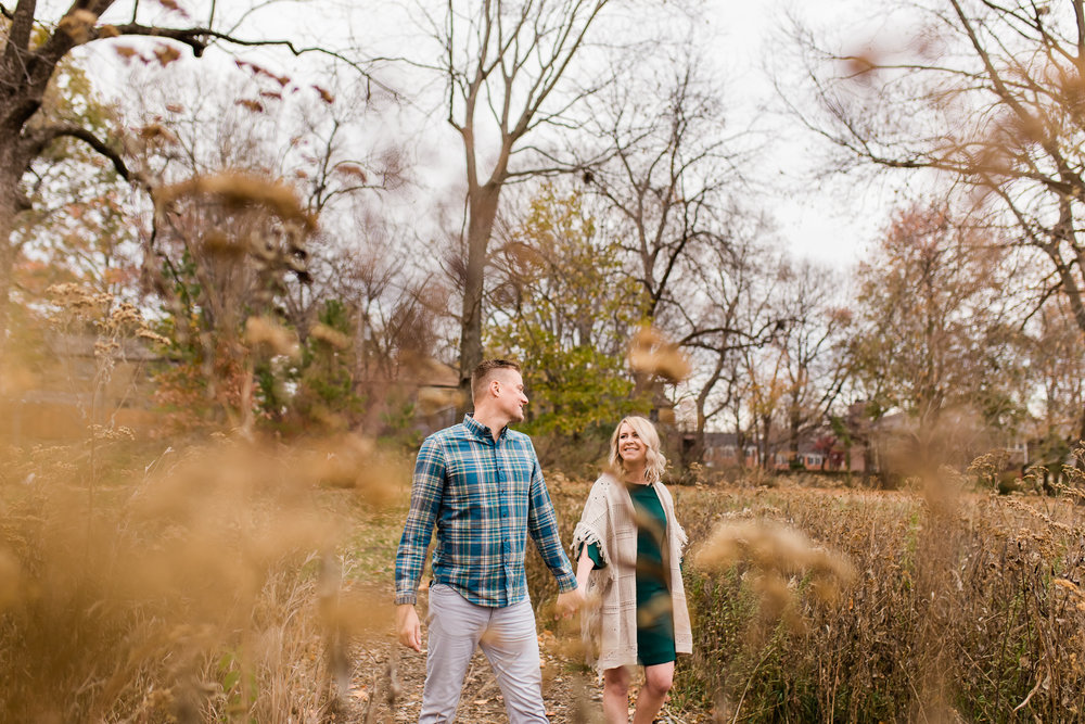 A couple holds hands as they walk through the field, Kansas City autumn mini couples session, Rebecca Clair Photography