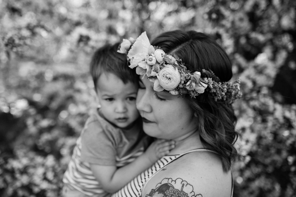 Black and white photo of mother cuddling her son under the flowering trees, Kansas City emotive family photographer, Loose Park, Rebecca Clair Photography