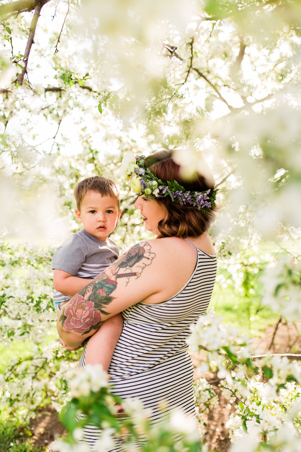 Mother holds her toddler son under a flowering apple tree, Kansas City mommy and me mini session, Loose Park in the spring, Rebecca Clair Photography