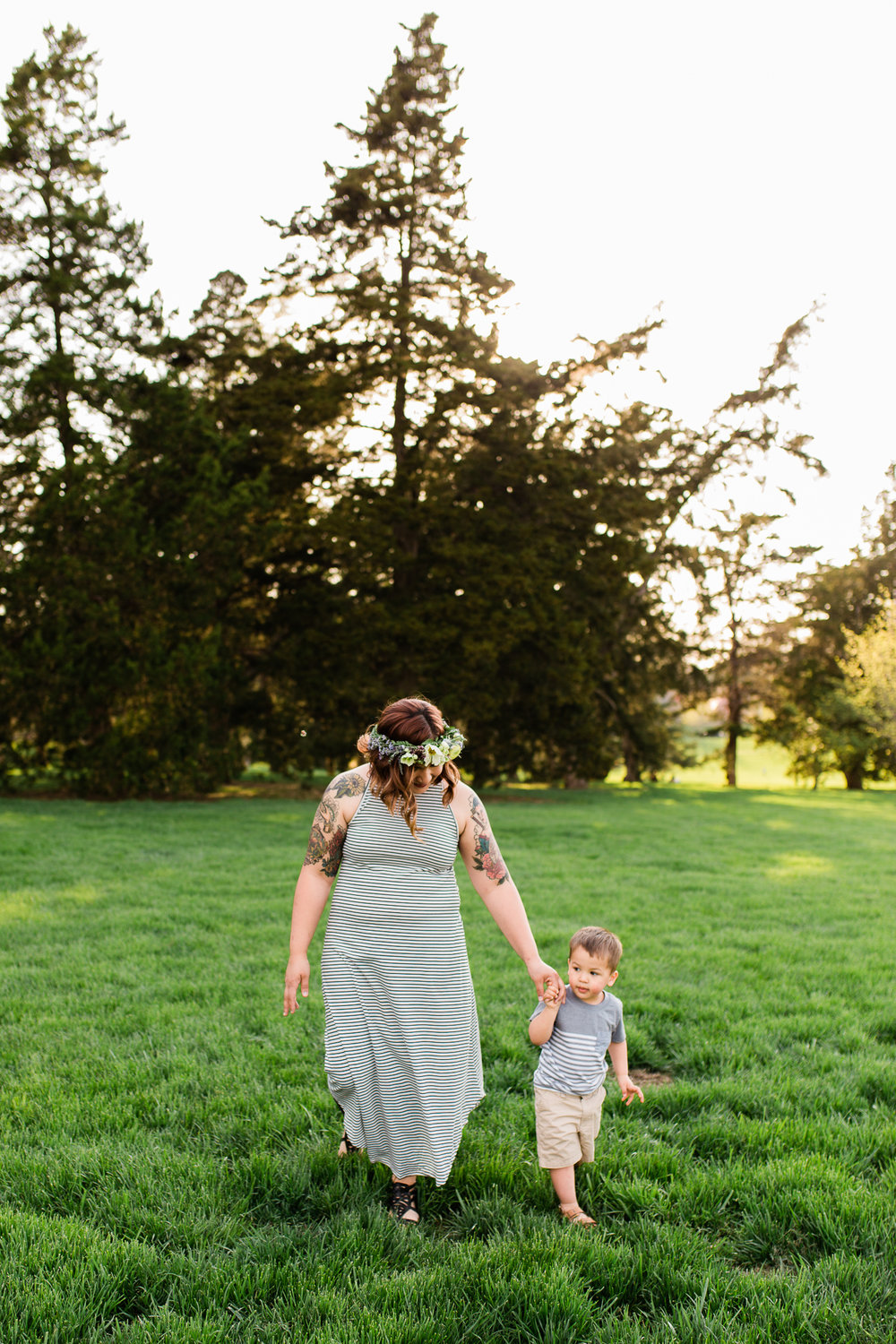 Mother walks with her son across the spring grass, simple family photos, Rebecca Clair Photography