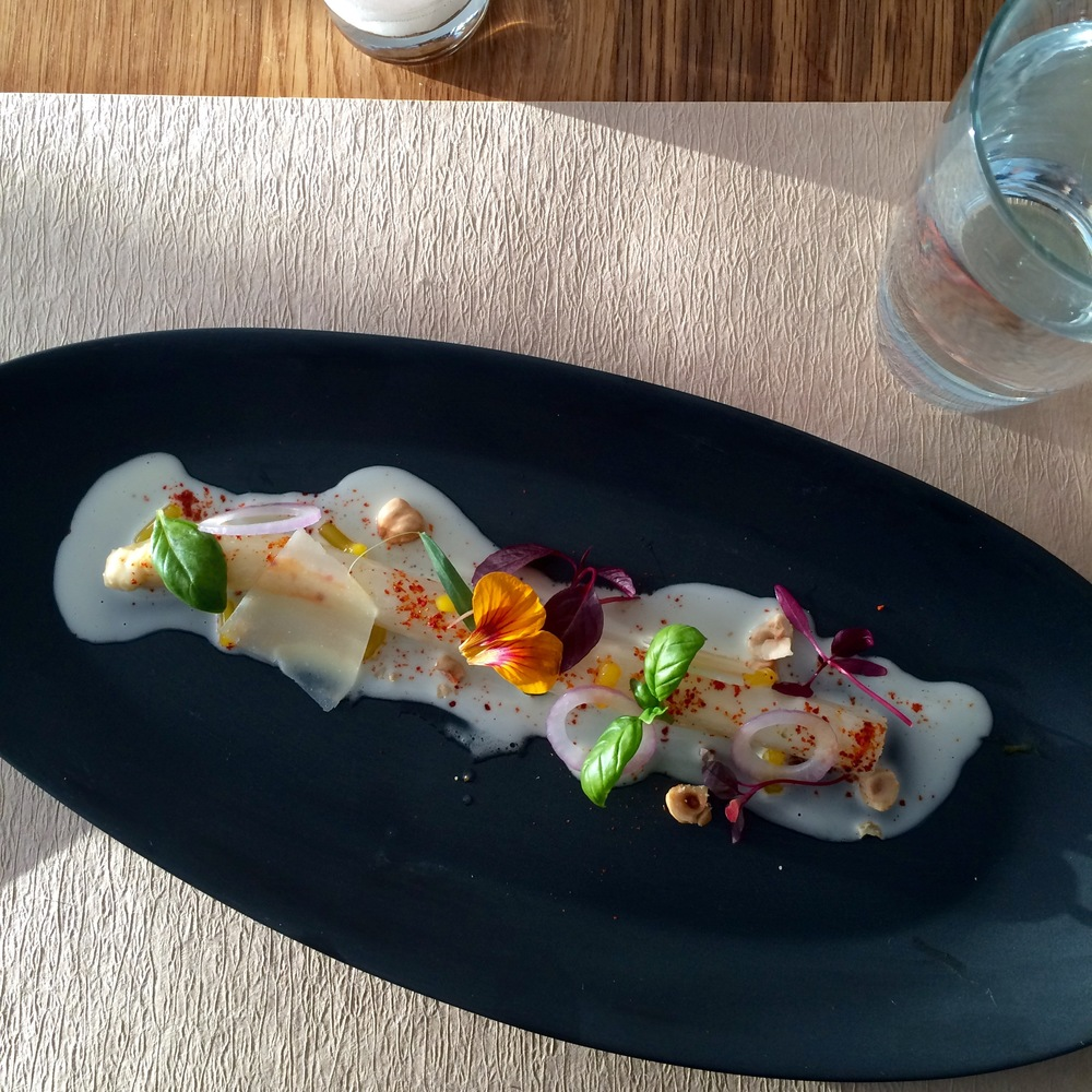 White asparagus, parmesan cheese, basil, edible flowers, and hazelnuts