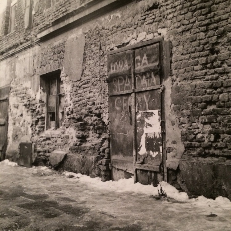 "Brick wall in an old Jewish Quarter in Krakow, PL. Deteriorating due to luck of funds for renovations. Sign on the door saying ""Alert Falling Bricks"".  Situation from 1991."