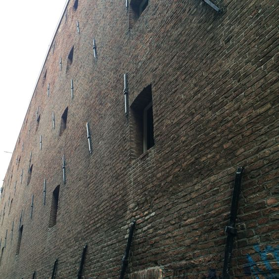 Side wall of the old warehouse building in Amsterdam. Sice it's construction it's been converted to loft apartments. Visible anchors holding wooden beams.