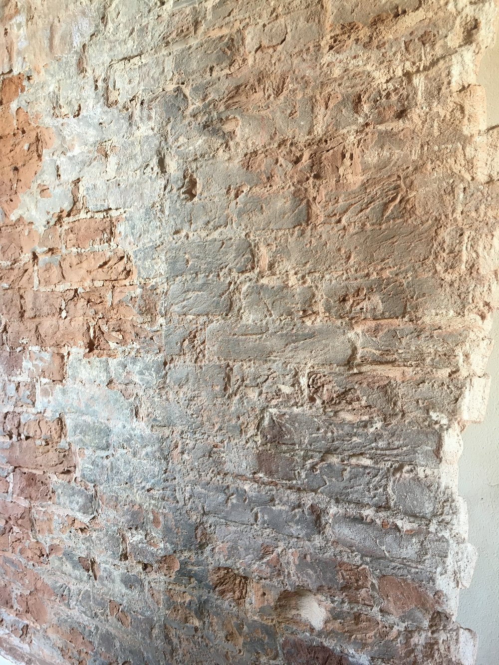 Old brick wall being exposed and cleaned.