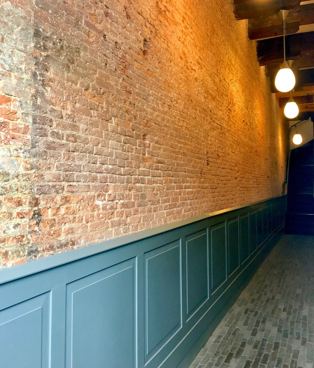Exposed brick wall and reclaimed brick on the floor of a corridor in loft apartments.