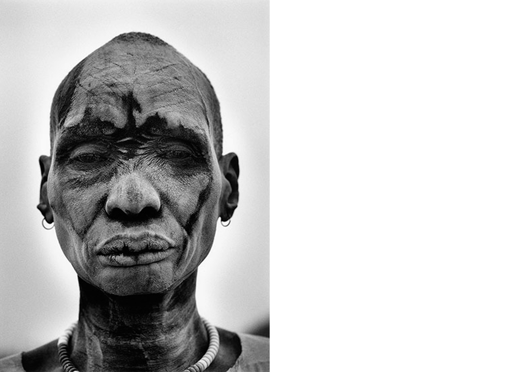 Dinka Man at the cattle camp of Kei. People cover themselves with ash from burned cowpats to sterilize the skin against insects and parasites, Southern Sudan, 2006/ Printed 2008  24 x 20 inches  Gelatin silver print