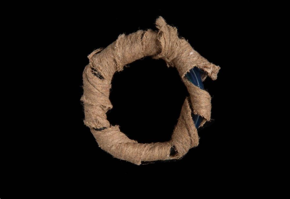 12. JAVA. Bracelet en verre enroulé dans une étoffe d'écorce battue entré dans les circuits d'échanges. Trouvé en Papouasie occidentale