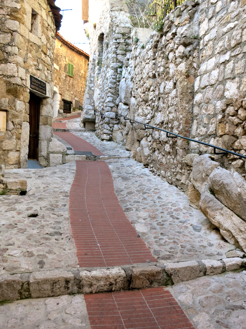 Handrails and a brick path help modern day tourists navigate the medieval village of Eze in the French Alps. © 2014 Gail Jessen