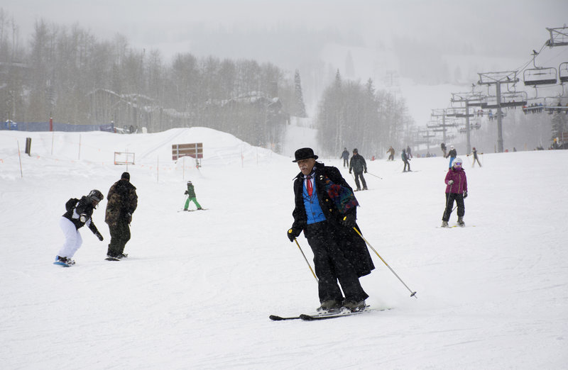 Art Clay, one of the founders of the National Brotherhood of Skiers, takes a run at Snowmass Resort in Colorado while wearing his traditional ski outfit - a black bowler hat and a black duster. SONYA DOCTORIAN for NPR