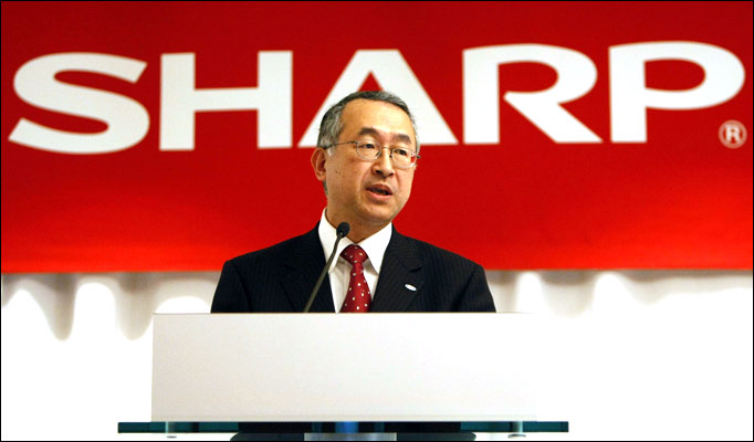 Toshihiko Fujimoto in front of Sharp sign