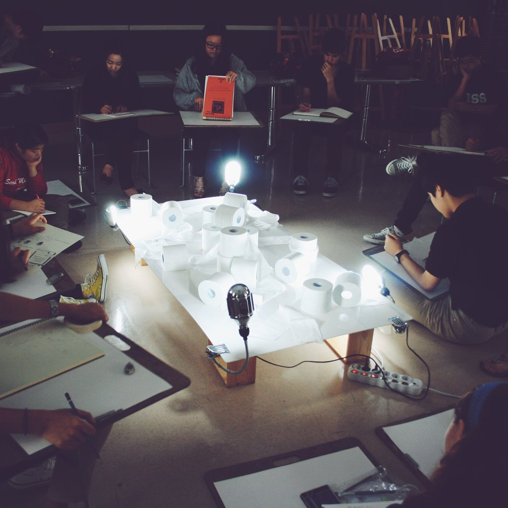 Students during a drawing unit creating from the exploration of light and value.