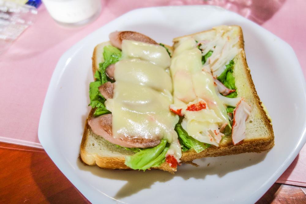 BREAKFAST SANDWICH: HALF SAUSAGE, CHEESE, AND LETTUCE, THE OTHER HALF CRAB MEAT, CHEESE, AND LETTUCE, BOTH WITH TUNA MAYO.
