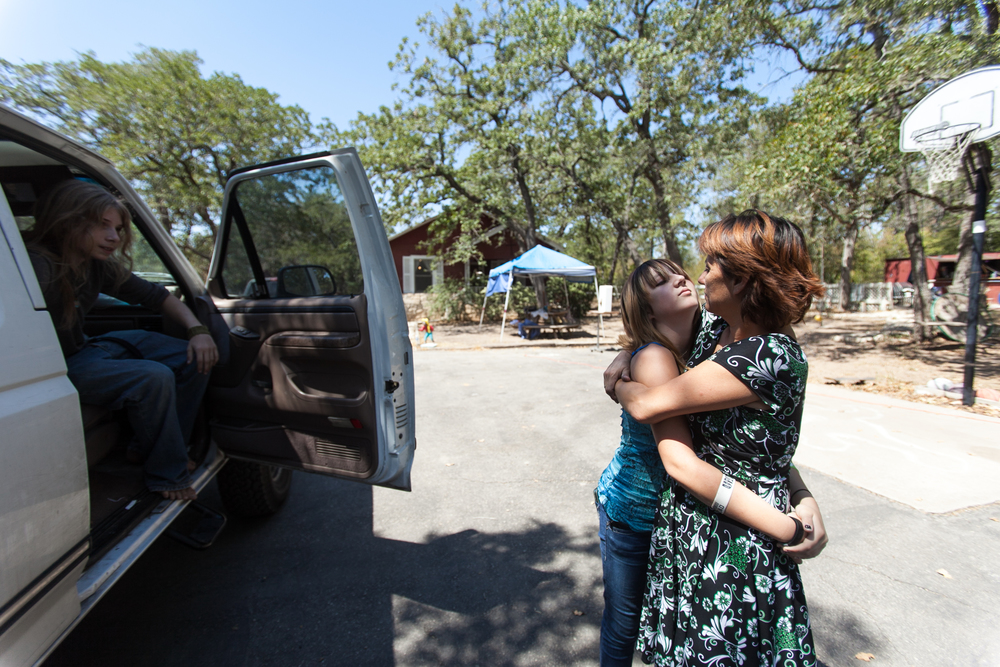 Patricia hugs her daughter Bailey as they arrive back at their house for the first time since the Labor Day fires. Their house was barely spared.