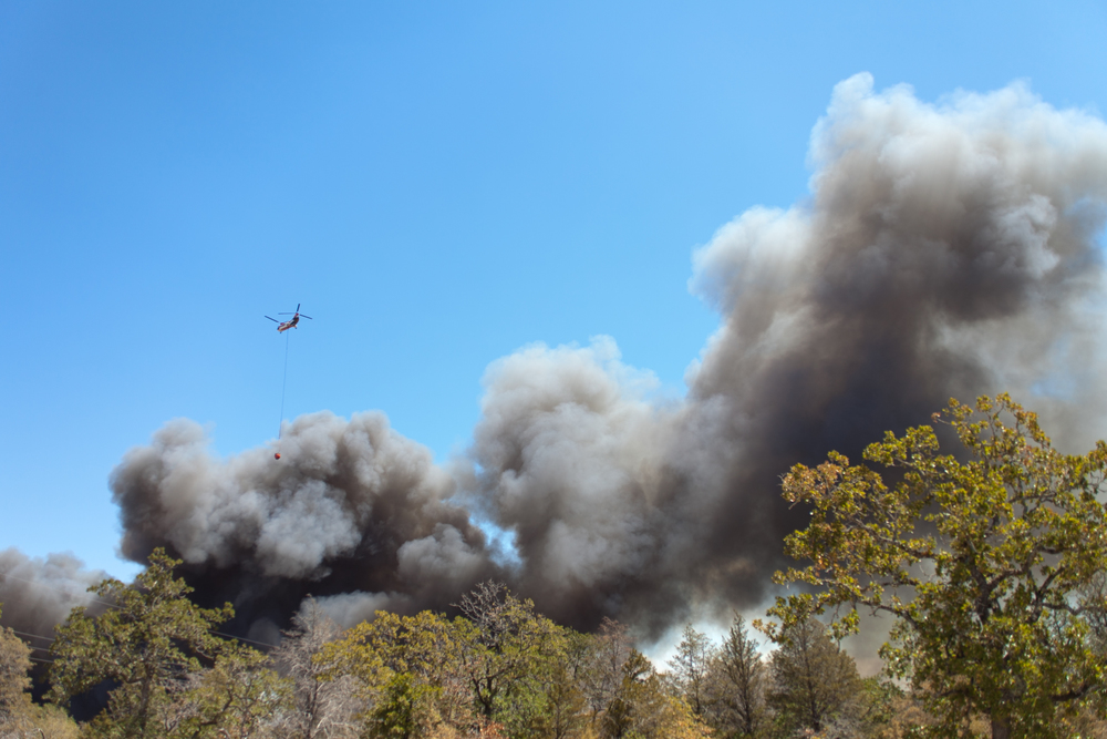 A firefighting helicopter flies above the smoke coming from the Bluebonnet Acres neighborhood in Cedar Creek, Texas.