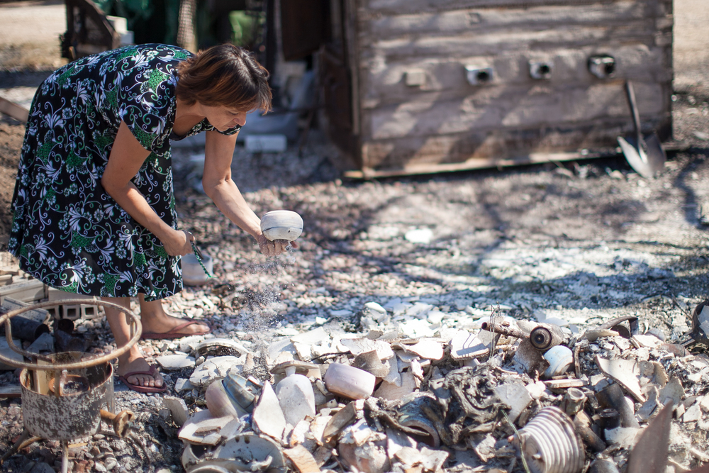 Patricia salvages pottery from a kiln on her neighbor's property. His home was burned to the ground while he was out of town.