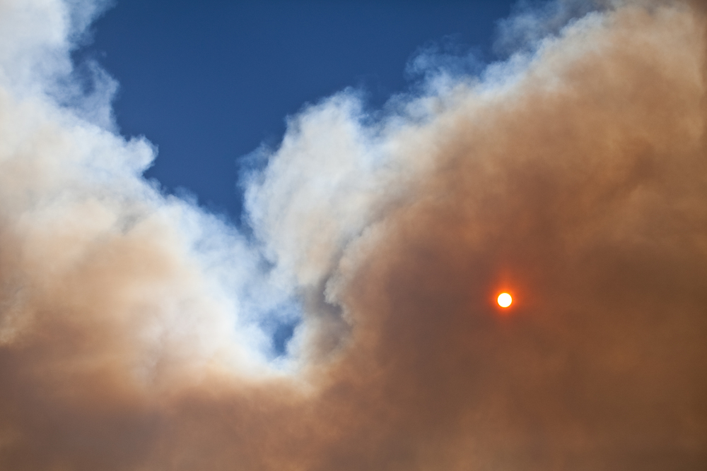 Smoke from a spontaneous fire covers the afternoon sun in October.