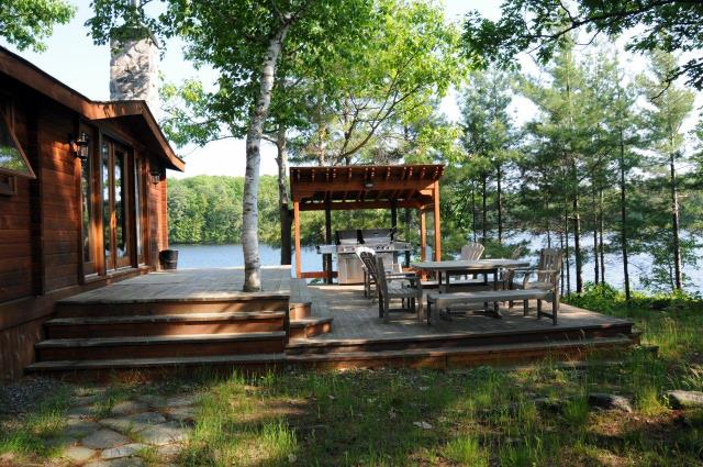 cottage deck with outdoor furniture and BBQ shelter - overlooking lake