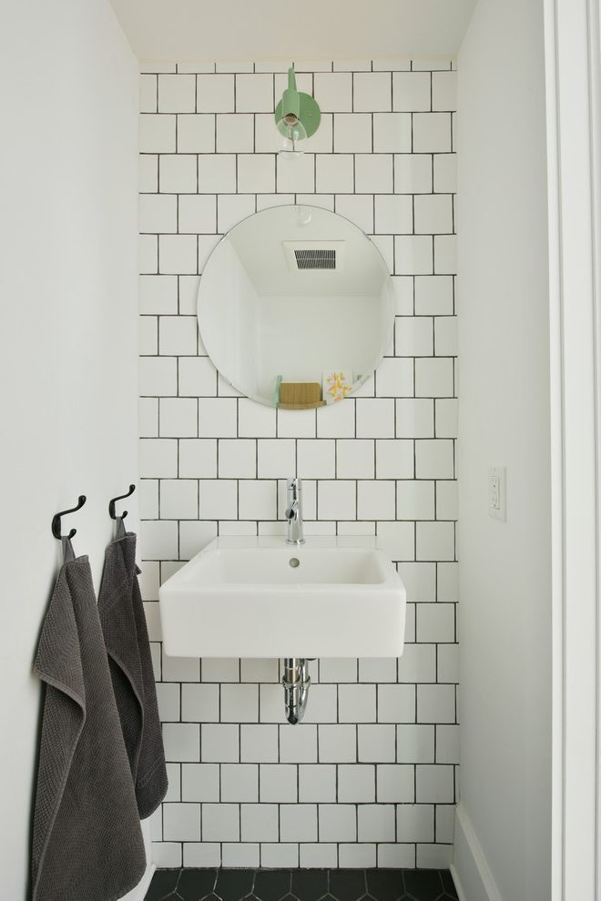 Very inexpensive tiles, with an Ikea mirror and a cheap and cheerful light makes for drama on a dime.