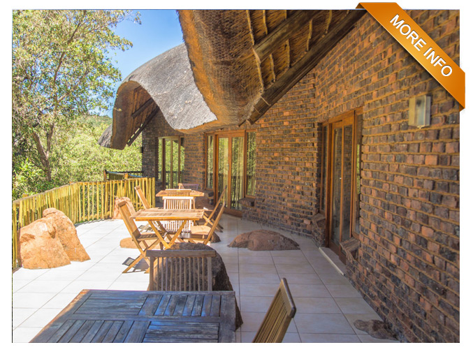 PRM032  |  R7 450 Per Night (R3 850 Per House) Sleeps 20 x guests in total (10 x per house) Unit consists of two houses interconnected by a central entertainment area - Each house comprises of * four bedrooms (two separate showers plus two separate bathrooms) * an upstairs loft with two single beds * open-plan kitchenette and sitting area opening onto large wooden deck - Central entertainment area entails * large indoor bar area with flat screen TV & DSTV * covered patio with Jetmaster built-in braai * swimming pool * enclosed boma Magnificent look out point  Game Drive Vehicle at optional extra cost per day PRICE: R7 450 PER NIGHT (R3 850 PER HOUSE)