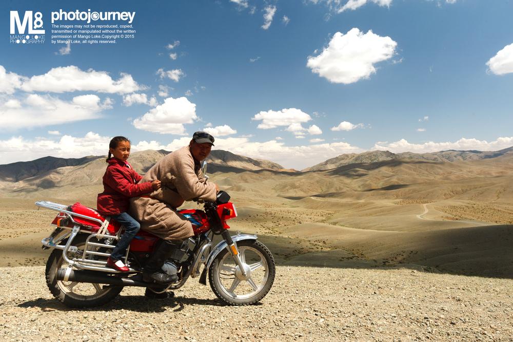 """大漠的父女.The Mongolian Father 蒙古. Mongolia. 2011 CANON1DMKIII 16-35MM F2.8L 1/160 F10 ISO200  炎热的天气底下,我们的车程已经走了好几小时. 一路上人烟稀少,导游司机突然把我们停在一处比较高的大漠山玻观看这辽阔又荒凉的大漠。此时一辆摩多机车从远处到来,机车上坐着一对看似父女的蒙古人. 蒙古父亲把摩多机车停下与我们的司机师傅喧寒了一番,然后往我们来的方向离去.一颗小点,在那辽阔荒凉的大漠,随着哪弯弯曲曲的路上慢慢的变小,然后在视觉上消失. 我与这一对父女有缘,不过就只是那么的一面之缘与一张照片名为""""大漠的父女"""""""