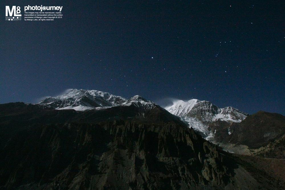 飘雪.星空.冷.The Night at Manang   尼泊尔. Nepal. 2009 CANON1DMKIII 16-35MM F2.8L 30sec F2.8 ISO3200   都是六年前的事了. 我与队友一团人,在安娜普纳路线行走了大概一星期到达了Manang,海拔大概3800. 这是一个需要停留至少一日来适应高原反应的地点. 当晚非常冷,时间是晚上11:33分。大伙儿都在食堂火炉旁取暖聊天,而我就拿了三脚架爬上了屋顶拍照. 穿着手套,厚厚又僵硬的手指就连要按个相机的快门也很麻烦. 当年我那部CANON1DMKIII表现良好,零下度数还可以拍照.ISO3200的杂讯还可以接受,粗粗的.不过现在回顾当年所拍的相片,那吵杂的粗点反而有了另一番味道.   话是说人需要向前望,然而,适时的回望反而能够将前路看  的更清楚.