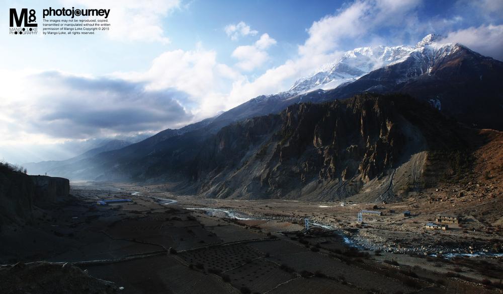 早上好马嚢.Good Morning Manang 尼泊尔. Nepal. 2009 CANON1DMKIII 16-35MM Panorama Stitching  每次背包出游,生活作息非常规律,早睡早起,珍惜旅程的每分每秒,比起城市的生活,好上万倍. 到达马囊的第一天就起个大早. 一个人漫步于石屋区的小路,探讨当地人们的生活作息文化. 3800海拔高度,空气开始稀薄,步行不能太快,会累死人的. 我顺着石屋之间的小路,慢慢的走到了视野辽阔的一个悬崖边. 站在悬崖边放眼望过对面的雪山,此时远方的晨光正好穿过云层形成耶稣光,整个画面真的很美丽,很壮观。早起,真好啊!