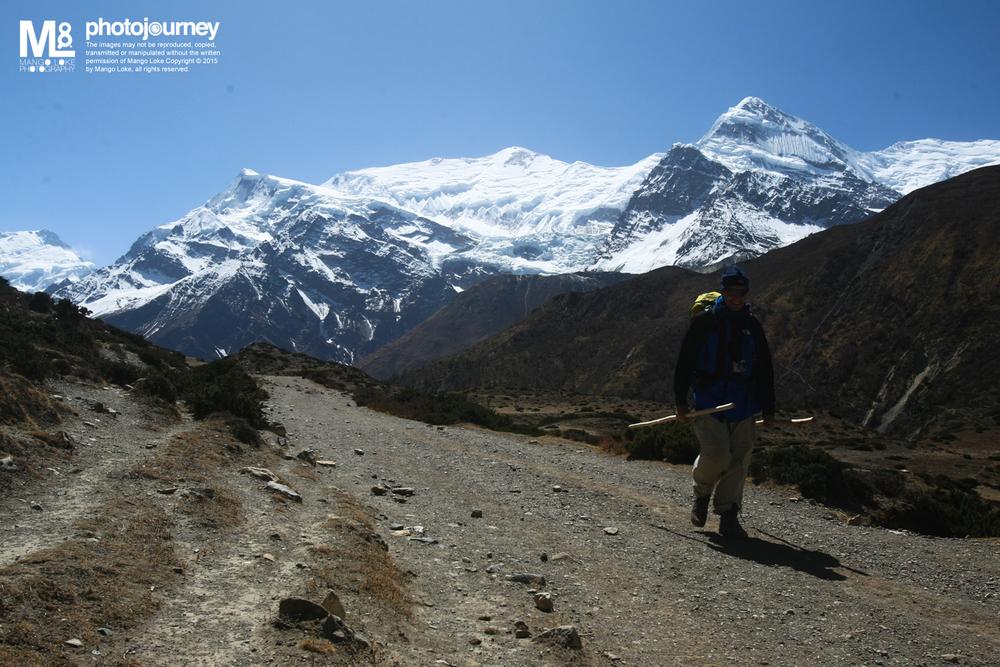 """人生,每个转弯都是惊喜.Life, Every Corner is a Surprise 尼泊尔. Nepal. 2009 CANON1DMKIII 16-35MM 1/320 F7.1 ISO200  相中的是一位来自荷兰的大叔,与太太两人一起行走安娜普纳. 我们在路程中的一间民宿遇见,当时只有我跟他在暖炉旁取暖. 我拿出了香烟正想抽的时候,出之于尊重问他一声是否介意. 没想到他很直接的回答,""""对不起,我很介意"""" 我有少许愕然,只好把香烟收起.通常如此的问,对方都会一样出之于尊重会不介意. 然后他说,介意是因为他是一位患癌的人,医生说他剩下的时日并不多,趁着还可以走动的时候与她太太一起走走看看这一个世界,现在已经走了四个月多了.  那一天过后,我们都没有再同在一间民宿遇过了. 直至Manang过后,在路上再次遇上了他. 我问他一切都还好吧? 我们坐在路边的大石上休息聊了一会,他笑着的跟我说,""""life, every corner is a surprise"""". 然后就继续的向前走去. 看着他那健步,一点也不像是个患癌的人.,我也没有想太多,拿出我的香烟,慢慢的抽着,他身影渐渐远去,然后转进了另一个山口.   我不懂他是否真的是患癌病人?或只是介意我在他面前抽烟而骗我?不过他那句话,在某一些时候,的确是影响了我."""