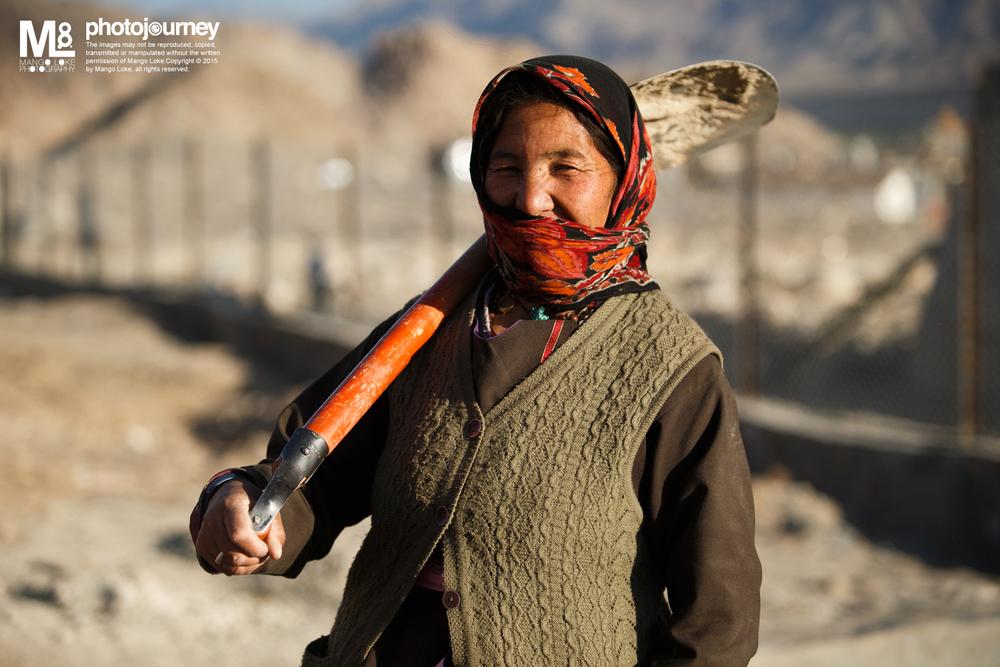 工地妇女.The Lady Worker   India 2013CANON 1DX70-200mm F2.8L 1/2500 F2.8 ISO500   那是一群北印的妇女,围着头巾半盖面 摃着泥铲,锄头,铁锤,于沙尘滚滚的路旁 一锄一铲一搬一抬,干着男人干的粗活 没有漂亮华丽的衣服,不经粉饰粗燥的面孔 隐隐可见那戴着结婚戒指的手掌摃着铁铲 面对着镜头,露出一面和蔼可亲的温柔神情  对于漂亮与美丽,自己有着一厢情愿的见解. 漂亮亮于外在,美丽美于内在. 漂亮亮于养目,美丽美于欣赏 漂亮亮于精致的装饰,美丽美在动人的典故 漂亮亮于青春年华,美丽美在岁月留下的痕迹 漂亮不等于美丽 美丽,有时候甚至乎说不上漂亮.  这一位刚柔并齐的妇女,美丽极了.