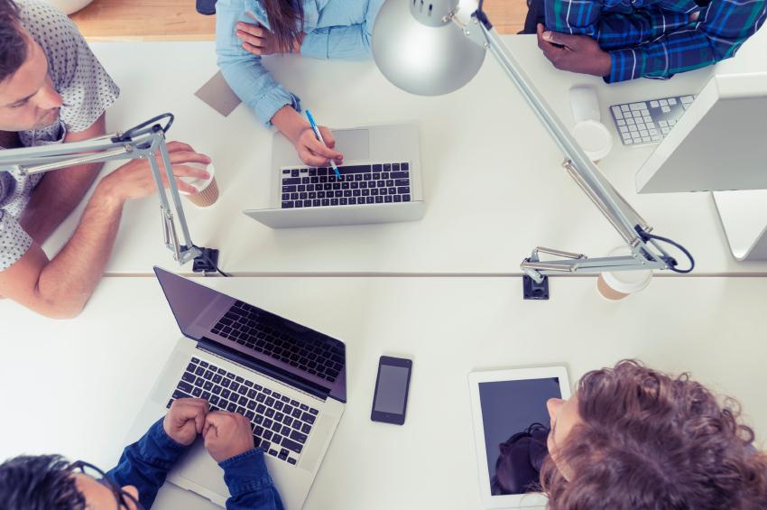 Team meeting around computers at white desk.jpg