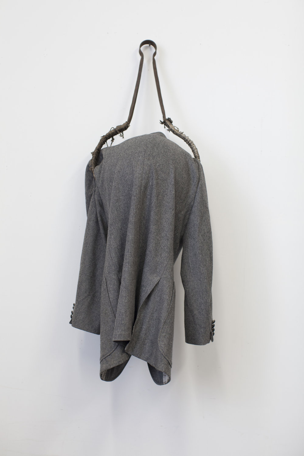You're Late, Found suit coat, metal, rope, plastic globe, 2018, 46 x 17 x 14 inches.