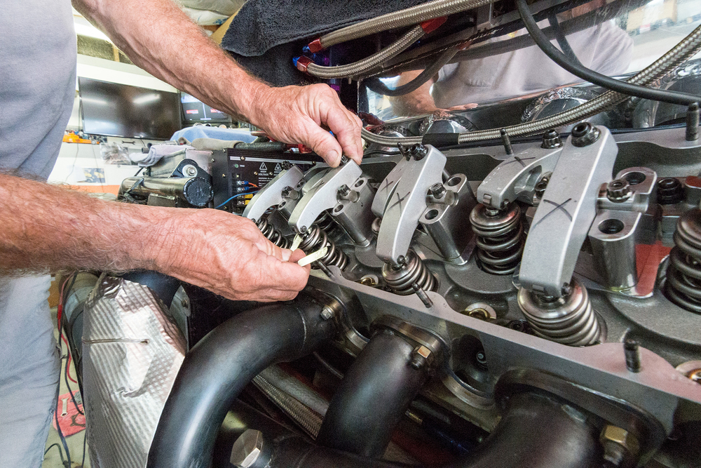 Dave Isley uses a feeler guage to check and adjust the valve lash, or the clearance between the rocker and the tip of the exhaust valve. The rockers open and close the fuel intake valves, and when out of adjustment, they hit and cause damage.