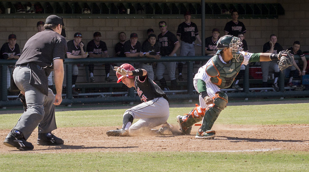 Pacific University freshman infielder/pitcher Cole Kanazawa scores in the top of the seventh inning during Sunday's game at Ben Hines Field as University of La Verne catcher Nikko Williams catches the ball too late. The Leopards did not score in the seventh inning. The Pacific University Boxers defeated the Leopards with a final score of 11-6. The next baseball game will be Friday, April 3, at Occidental College.