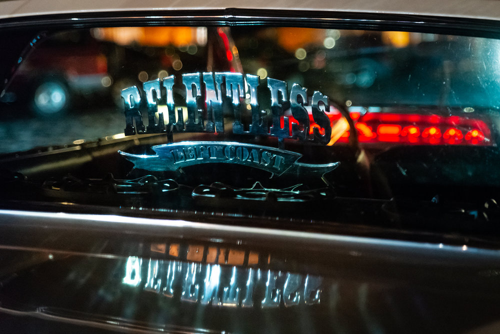 A Relentless Car Club plaque is illuminated by a passing car's headlights as the lowriders in Old Sacramento talk with each other before their final cruise home.
