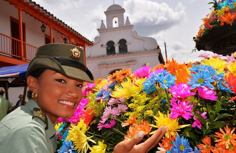 A policewoman besides some flowers at the 2014 Feria de las Flores. Source: Policia Nacional de los Colombianos, August 1 2014. Available here.