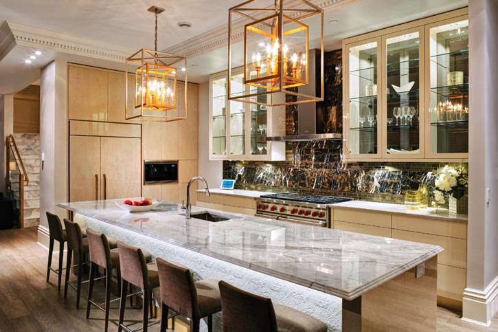 An entertainment and social hub, this kitchen is a study in contrast: dark marble backsplash and high-gloss natural millwork, gold mosaic tiling and gleaming stainless steel appliances.