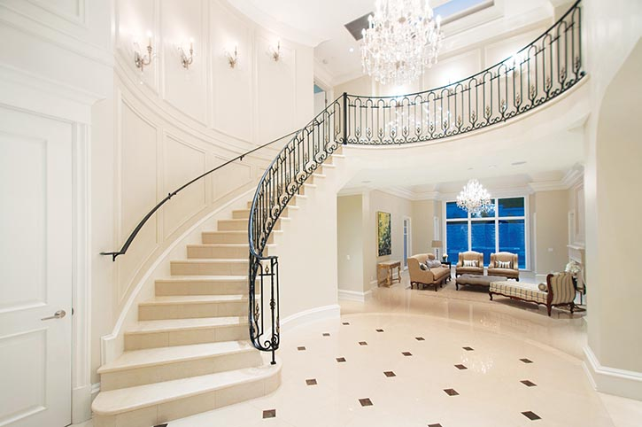 A Schonbek chandelier featuring Swarovski crystal floats above the foyer's inlaid white marble floor.