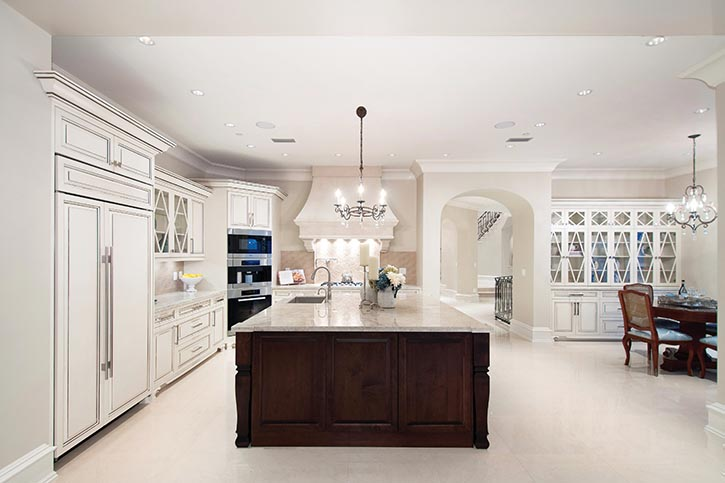 Antiqued white millwork with diamond-shaped detailing creates a culinary centre worthy of a king.