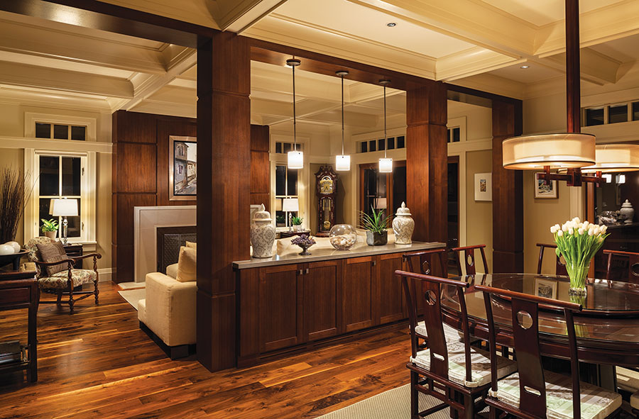 Columns crafted from custom millwork help separate the dining area from the family room, but keep the space open and airy. A panelled fireplace surround is a rich accent.