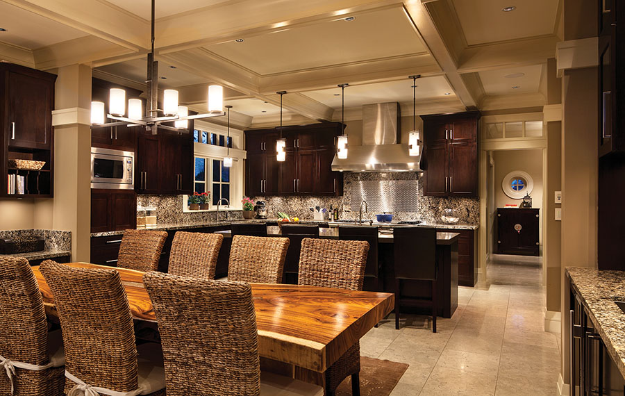 Reed-covered chairs, granite backsplash and countertops and a live-oak dining table are naturalistic touches in the eat-in kitchen.