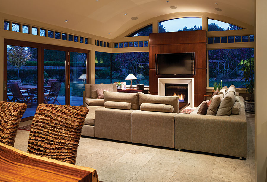 Connecting window edges in the family room create a continuous, transparent corner that appears to wrap the room in trees. The barrel-vaulted ceiling lends grandeur.