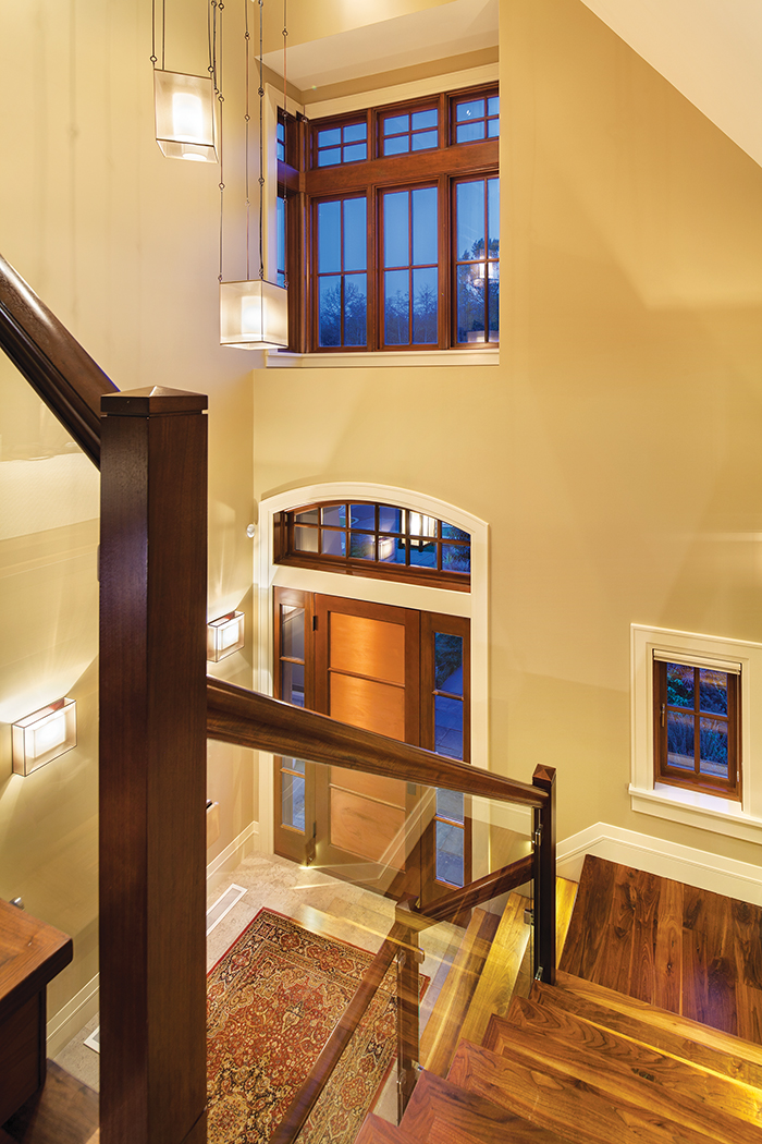 This home merges traditional elements such as dark wood banisters and clear glass railings.