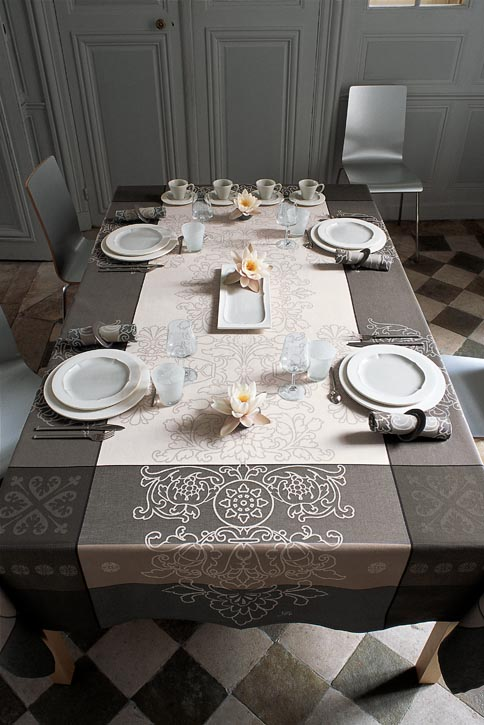 Ornate patterns seem etched into sandstone-colored blocks. The contrast creates polish without pomp. This design lays the foundation for simple elegance or makes way for something extraordinary. If you want to impress important acquaintances, choose this tablecloth and you can't go wrong.