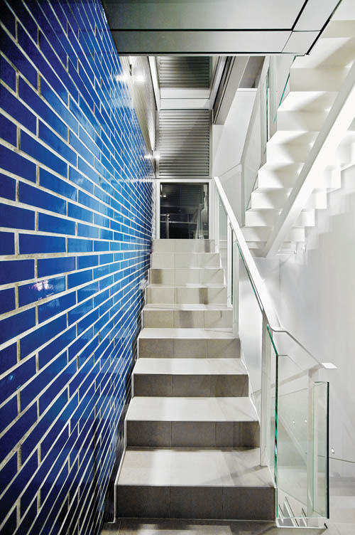 Glossy blue masonry is juxtaposed with muted greys, whites, and clear glass decor to striking effect.