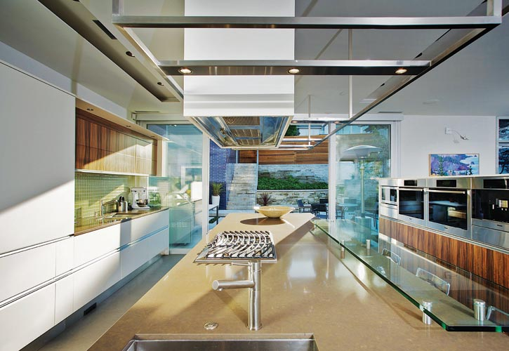 Sliding glass doors and a bank of appliances define the kitchen but don't inhibit its connection with the living spaces around it, indoors or out. Ocean blues and greens create a tranquil environment.