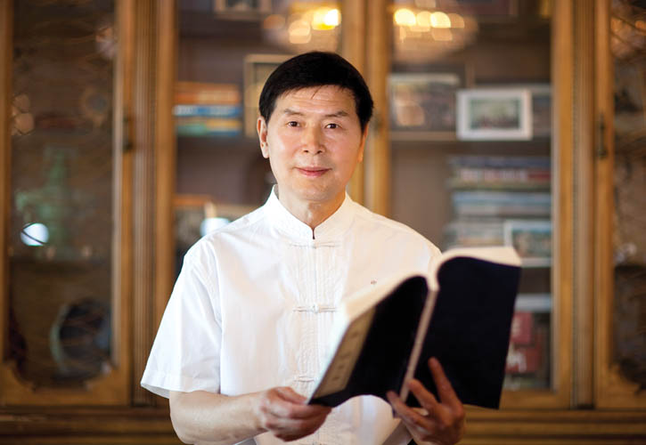 Li Youfu at home in Los Angeles, California, surrounded by ancient Chinese books.