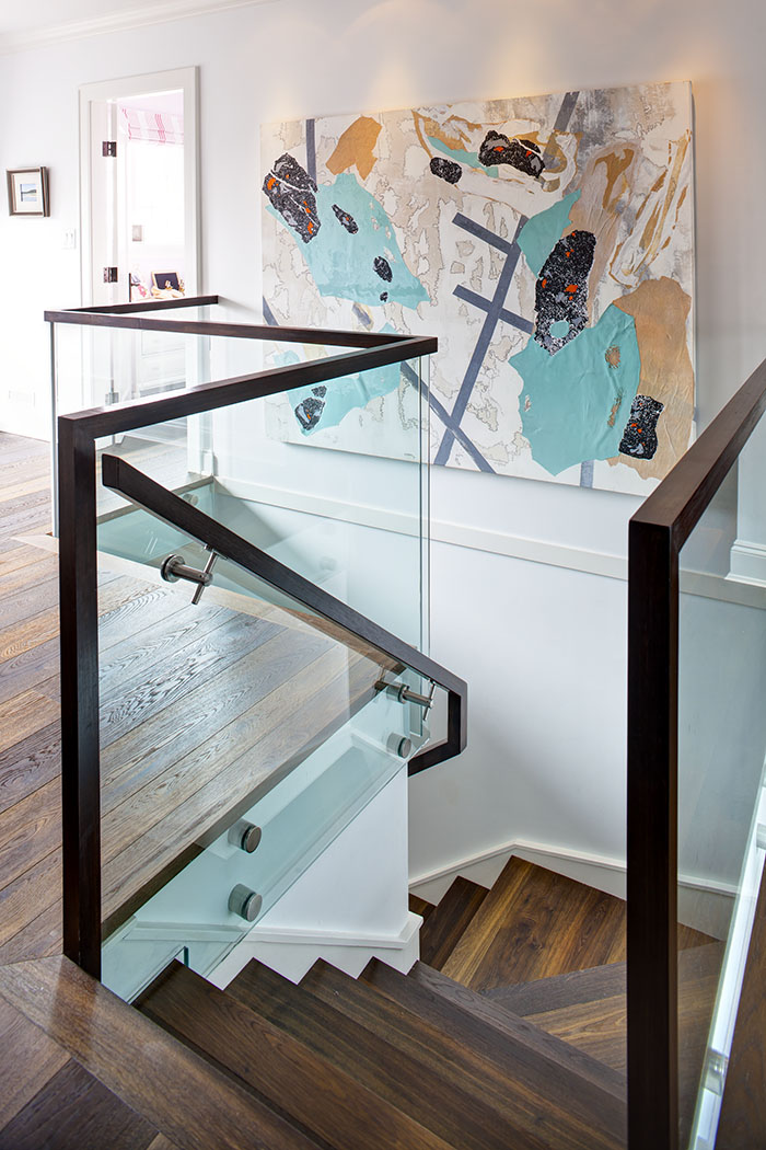 Polished wood risers and glass railings are an architectural focal point.